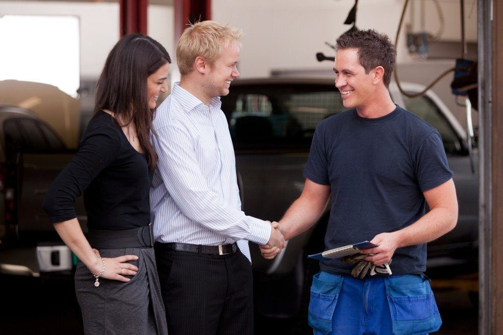mechanic and couple shaking hands
